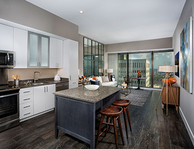 2Hopkins apartments kitchen with separate island with two hightop chairs, quartz counters, stainless steel appliances and white cabinetry and living room and large windows overlooking downtown Baltimore in the background