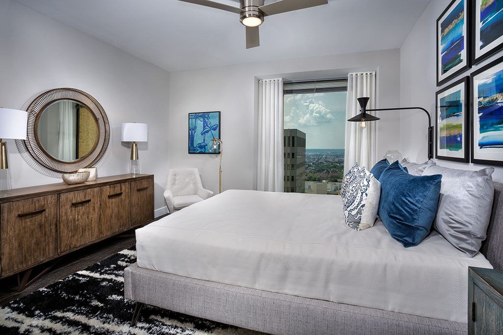 2Hopkins apartment bedroom with ceiling fan and city view