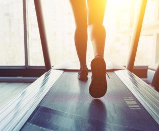 photo of woman's legs running on a treadmill as sun shines through window