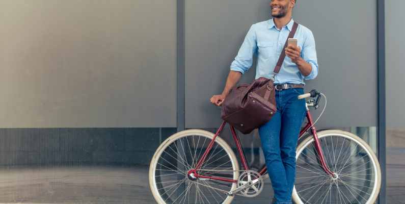 photo of main in jeans and blue shirt carrying a duffle bag and smart phone while smiling and leaning against a red city style bicycel