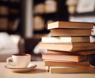 photo of a pile of old books on a table next to a coffee cup