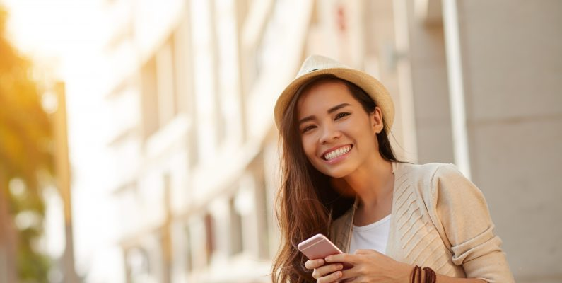 photo of girl in fedora smiling and holding a smart phone