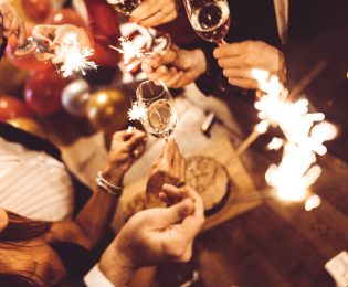 photo of people holding sparklers and wine glasses at a dinner party