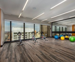 photo of 2Hopkins apartments' fitness center spin room with a row of spin bikes in front of windows