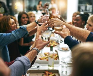 photo of dinner party and long table filled with table clinking glasses and bottles together while smiling