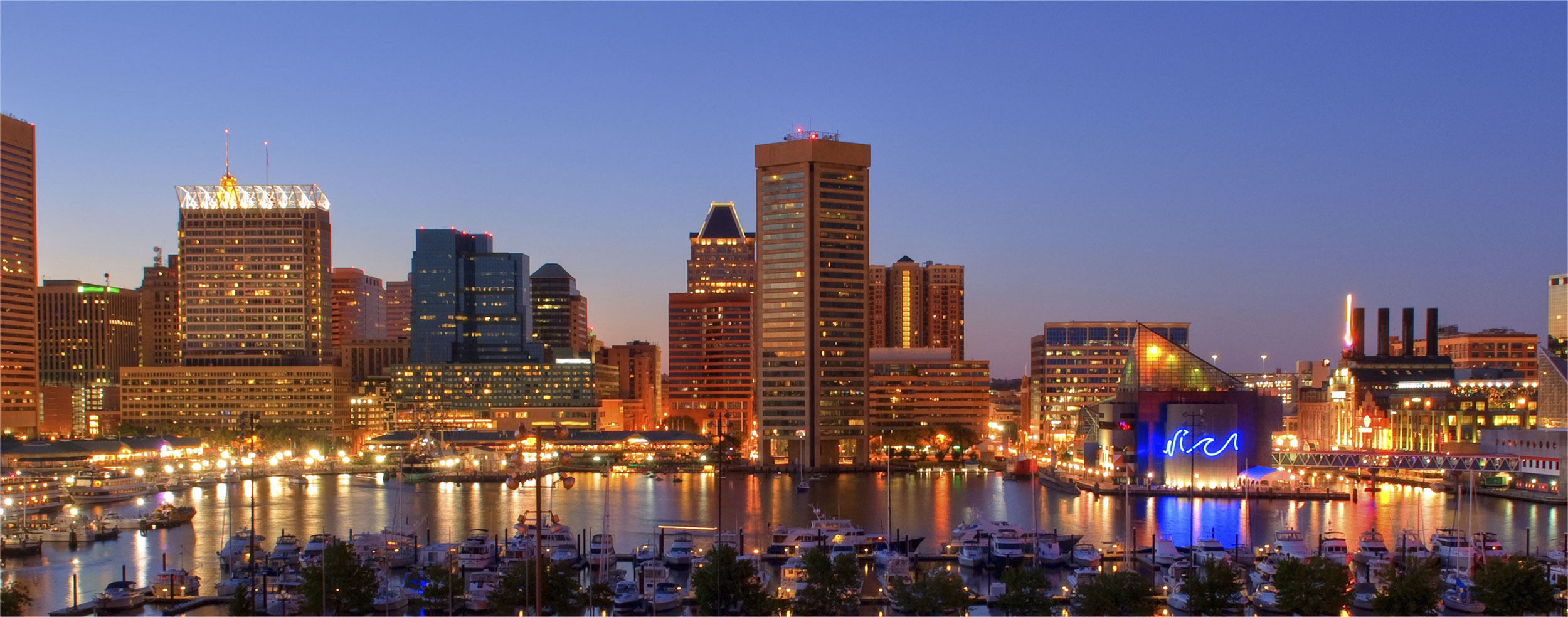 evening photo of downtown Baltimore skyline with marina in foreground and buildings in the background