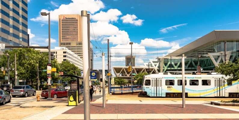 photo of downtown Baltimore with light rail train and convention center in background