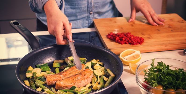 photo of man with tongs in kitchen cooking salmon filets with asparagus and zuchini in a pan with other chopped vegetables in bowl and cutting board next to stovetop