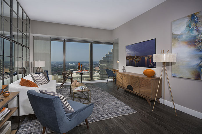 photo of 2Hopkins apartment living room interior with rug, couch, chair, end tables, floor lamp, TV stand, small dining table and chairs and window open overlooking downtown Baltimore